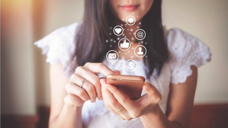 mujer interactuando con las redes sociales en su celular