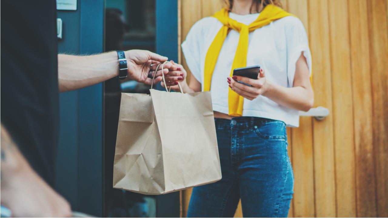 repartidor entregando un producto a una cliente en la puerta de su casa