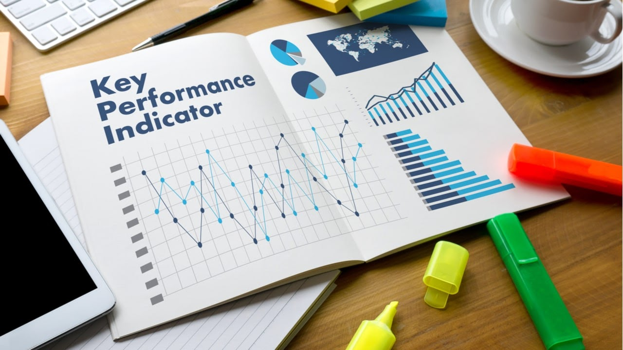 texto key performance indicator escrito en un cuaderno abierto encima de un escritorio