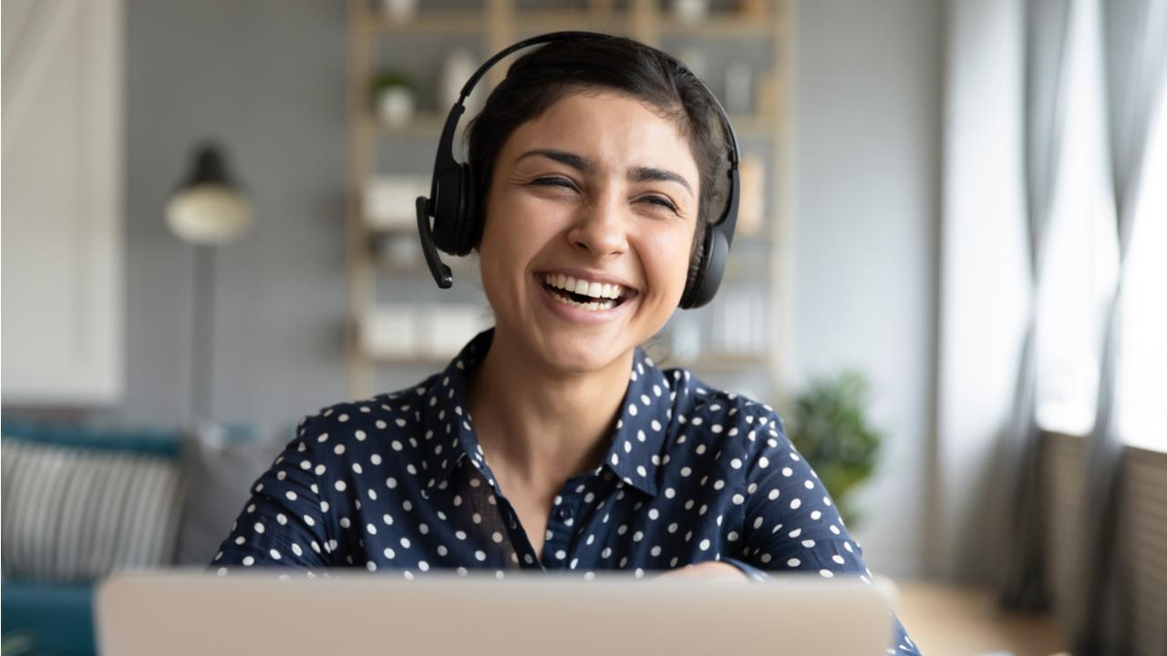una joven trabajadora sonriendo frente a una laptop